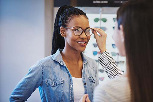 Optometrist fitting glasses on an attractive African American woman customer inside a store as she selects a frame